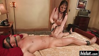Busty mistress Daphne Rosen plays with her male slave